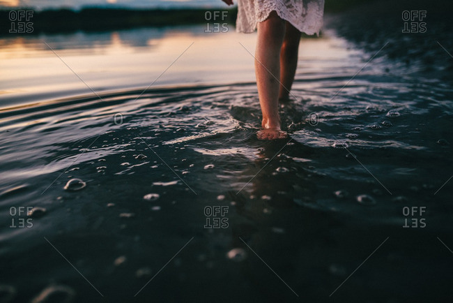 Legs of a girl walking in a shallow lake