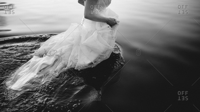 Bride in her gown walking in a lake