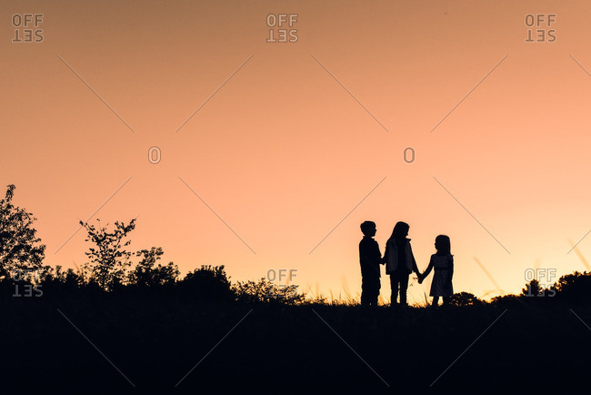 Silhouette of children holding hands at sunset