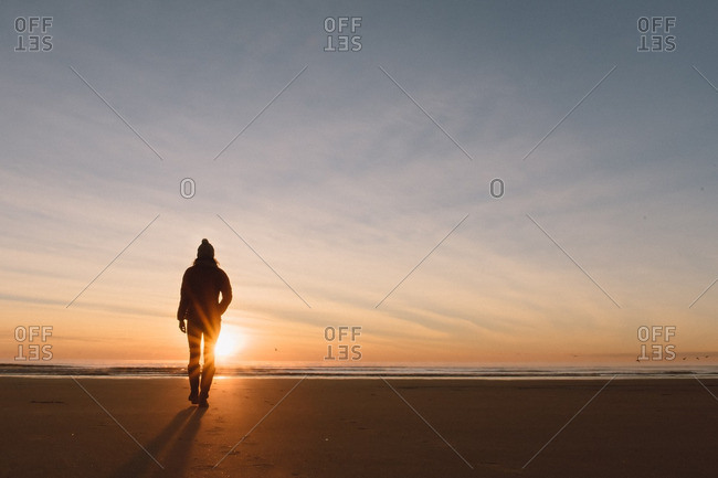 Silhouette of woman on a beach at sunset