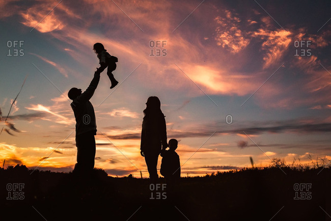 Silhouette family in a field at sunset