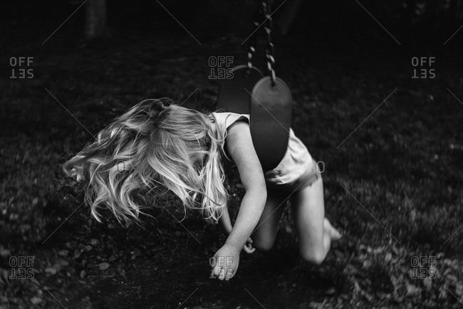 Little girl lying on her belly on a swing