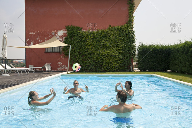 Family playing with ball in a pool