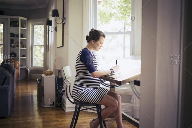 Pregnant woman at drafting table