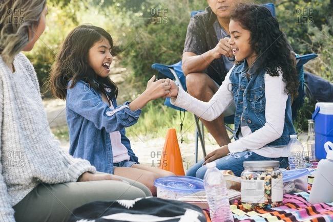 Girls at picnic having thumb war