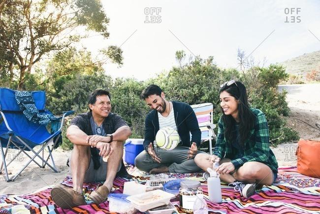 Three adults at beach picnic
