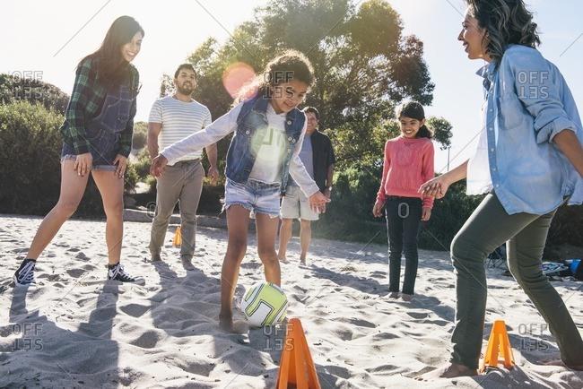 Girl scoring goal at beach soccer game