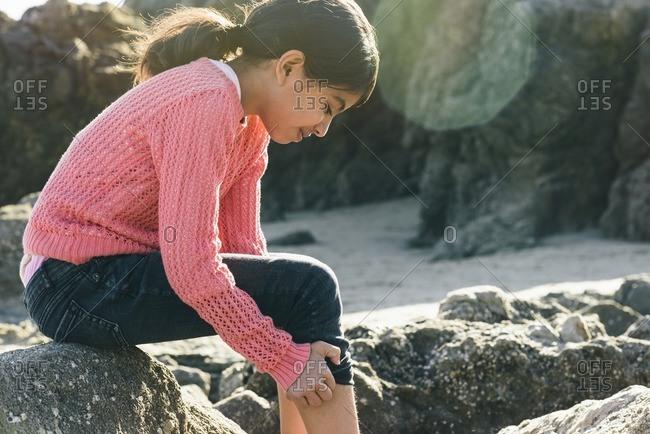 Girl pulling up jeans leg on beach
