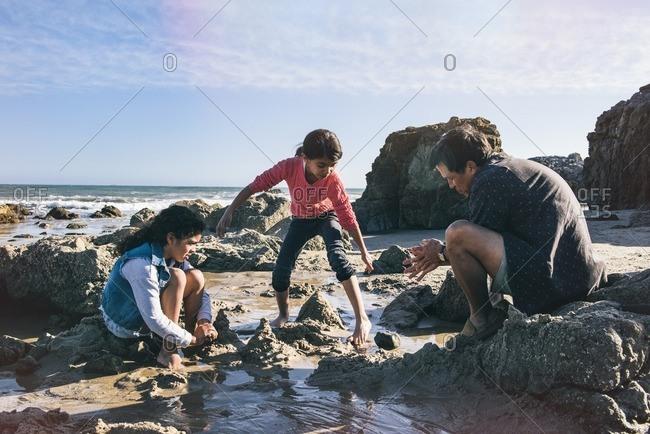 Man helping girls build sandcastles