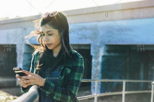 Hispanic woman using phone on beach