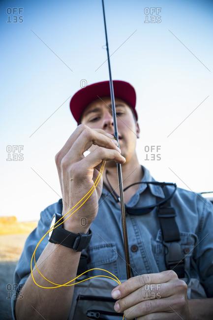 Man stringing line on a fishing pole