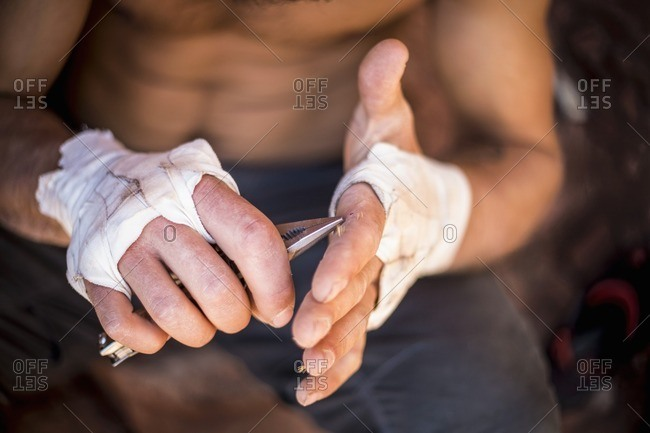 Man pulling splinters from his hands with pliers