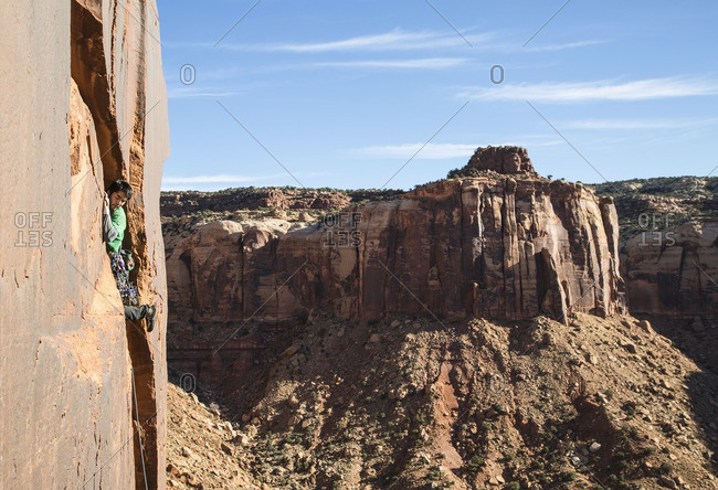 Man climbing up the side of a mountain