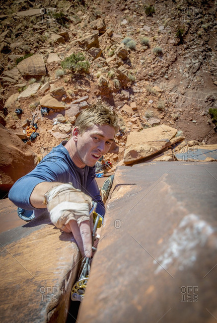 Man putting cam into rock gap while rock climbing