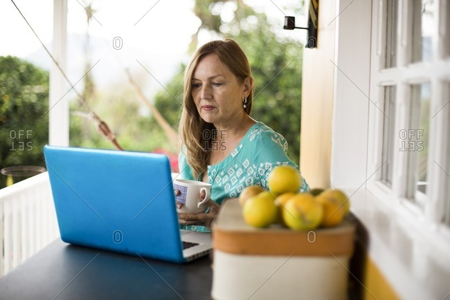 Woman with a coffee using laptop