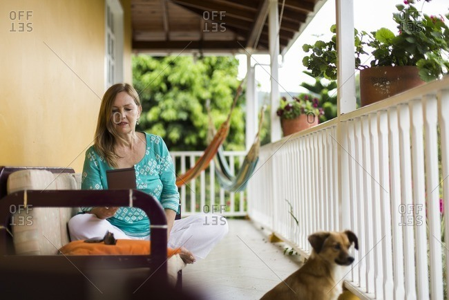 Dog by woman on porch with tablet