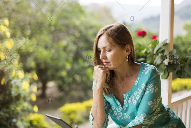 Woman on rural porch with laptop