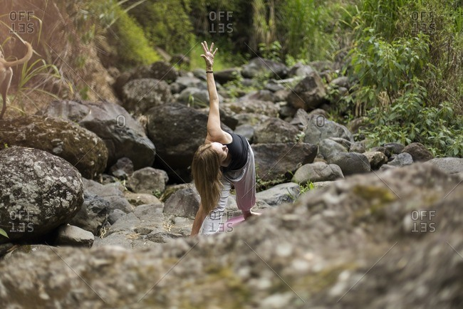 Woman doing yoga on forest rocks