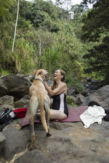Woman in forest laughing with dog