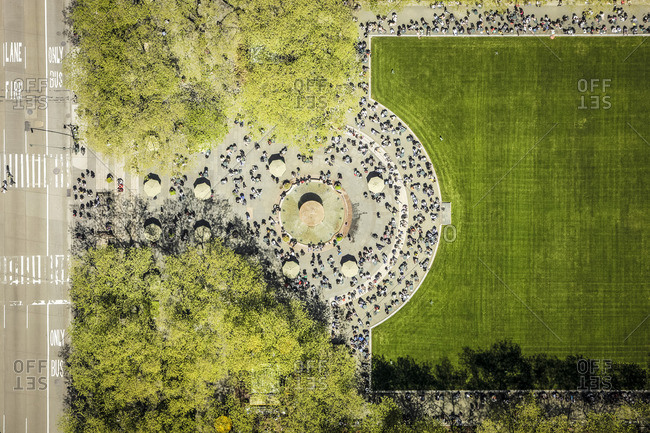 Aerial view of people surrounding a green expanse in an urban park