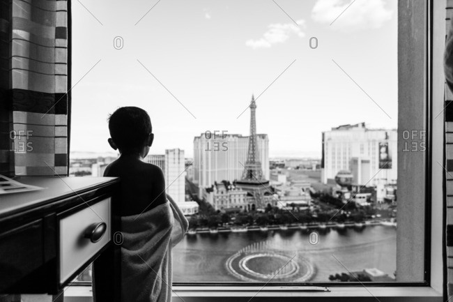 Las Vegas, NV, USA - July 14, 2016: Boy at window with a view of the Paris hotel