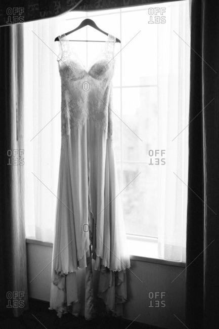 Bride's wedding gown hanging in a window