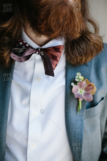 Groomsman with a red bowtie and boutonniere