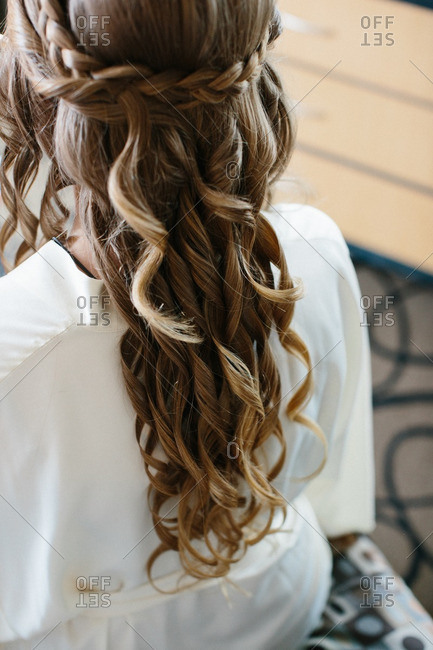 Bride with a curled hairstyle getting ready for her wedding