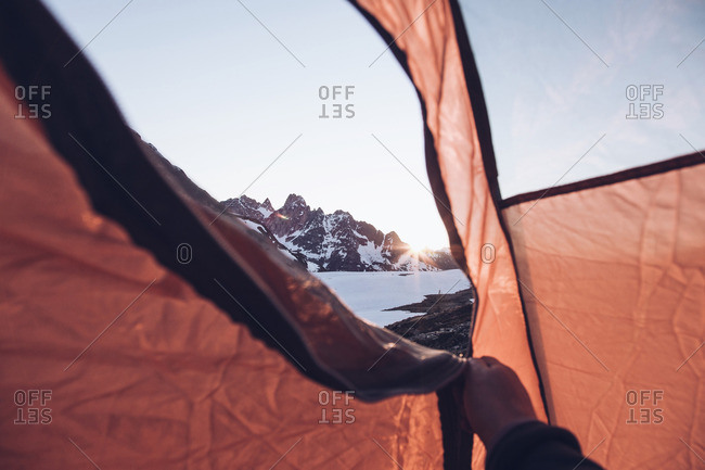 Hand opening tent in mountains