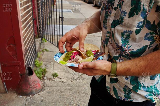 Man standing outside on a sidewalk eating a plate of pork carnitas