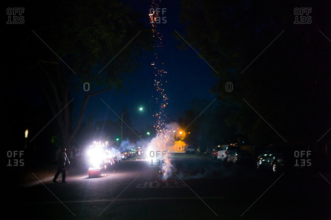 7/5/16: Man lighting fireworks in the street at dusk on Independence Day
