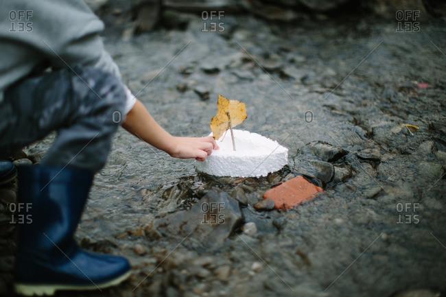 Close-up of a boy's hand letting a Styrofoam leaf boat go down a stream