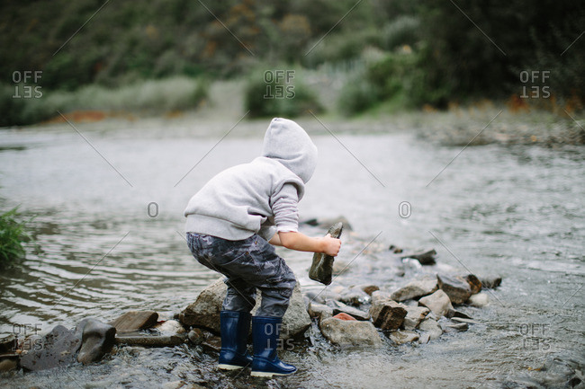 Boy in a hooded sweatshirt and boots making a rock barrier in a creek