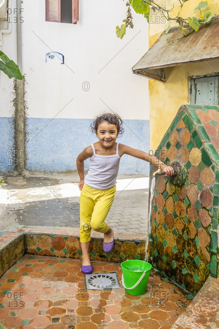 10/29/14: Girl getting water from a colorful outdoor well in Tangier, Morocco