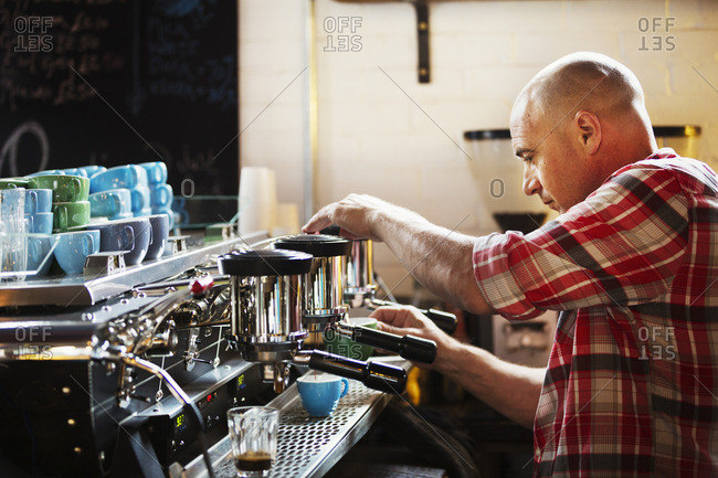 A man working a coffee machine making coffee