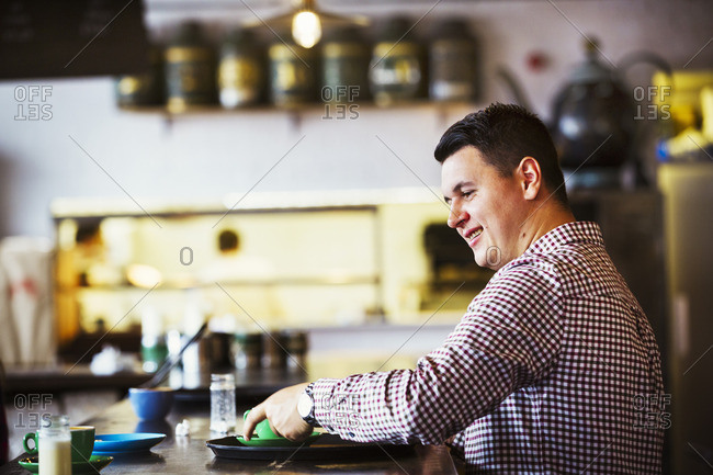 A man seated at a counter with a cup of coffee