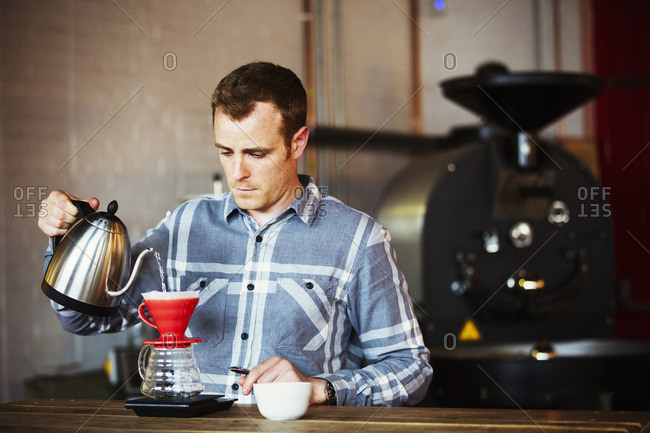 A man brewing coffee using a filter paper, and drinking it