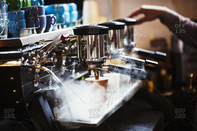 A person working at a large coffee machine, with three percolating containers, handles and a pipe sending out steam