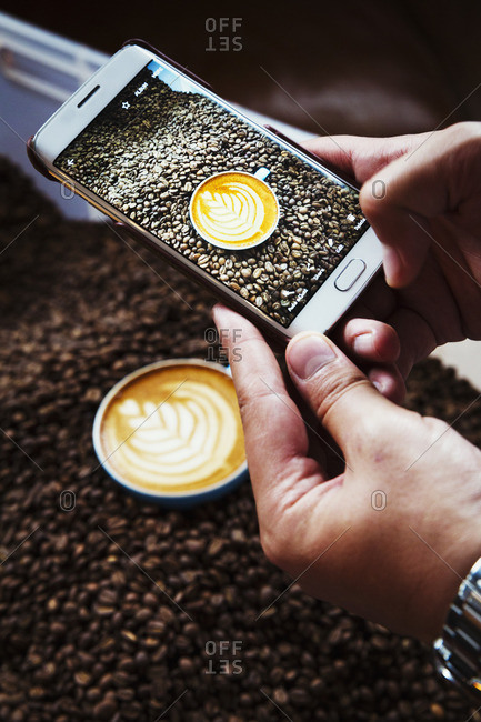 A person taking a picture with a smart phone of a cup of coffee on top of a heap of roasted coffee beans
