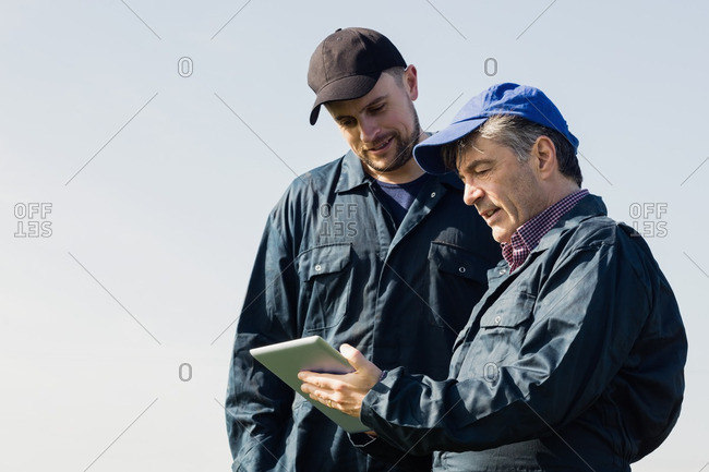 Farm workers discussing over digital tablet against clear sky