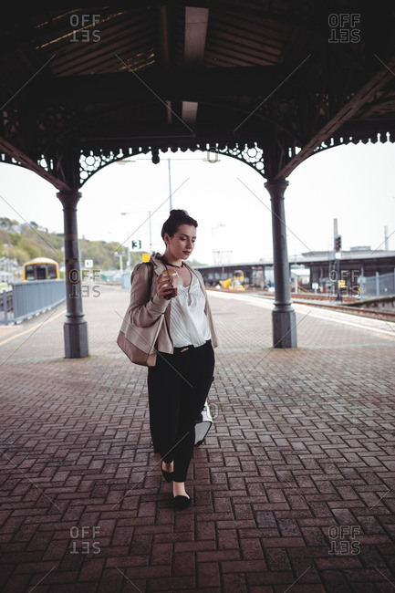 Full length of young woman with luggage at railroad station platform