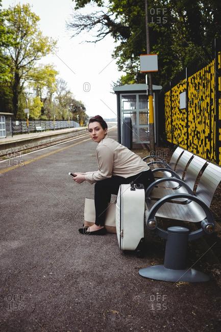 Beautiful woman sitting on bench at railroad station platform