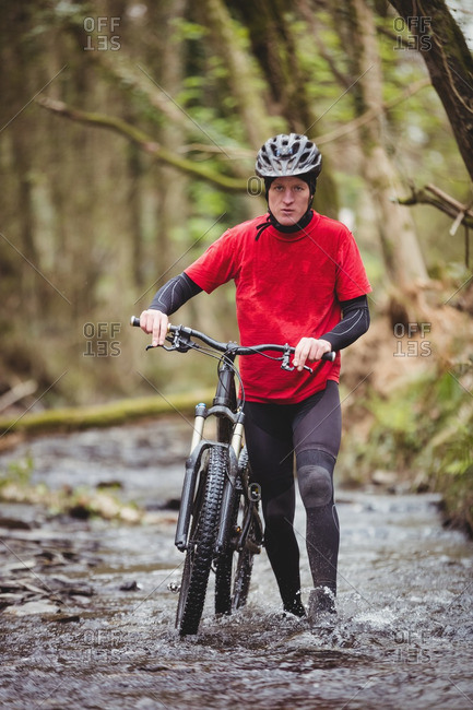 Portrait of biker walking with bicycle in stream at forest