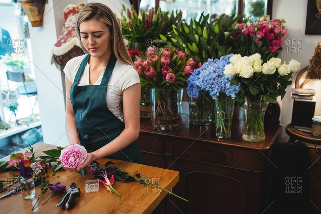 Female florist preparing a flower bouquet at her flower shop