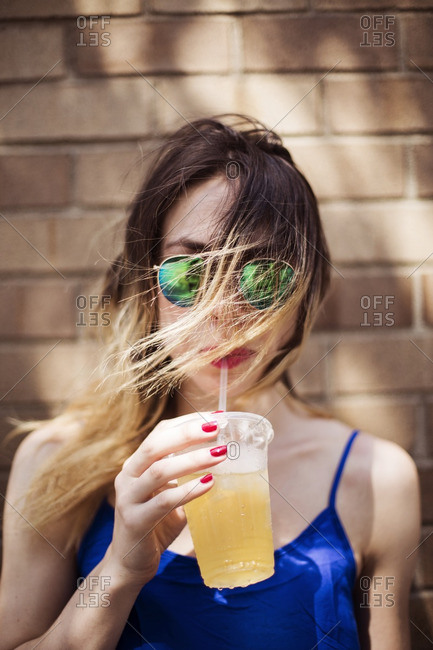 Portrait of woman drinking juice from disposable glass against wall