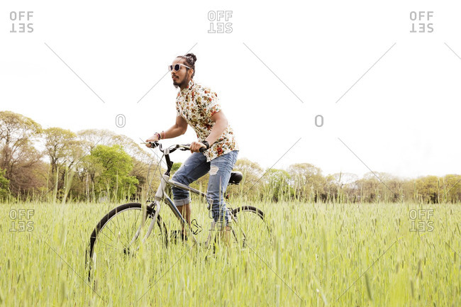 Man riding bicycle on grassy field against clear sky