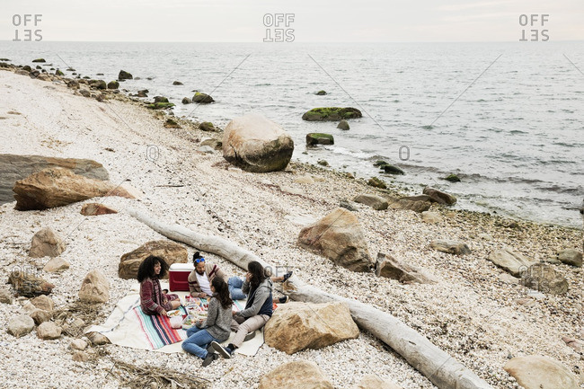 High angle view of friends enjoying picnic on beach
