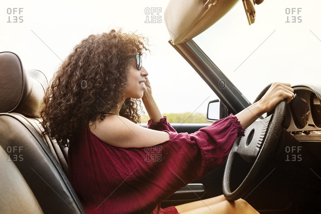Side view of smiling woman driving car against sky