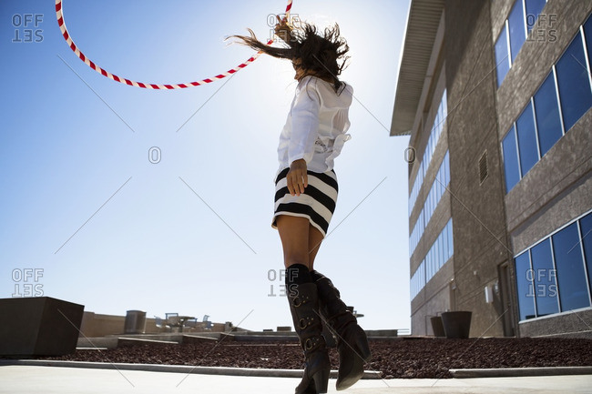 Woman playing with plastic hoop against clear sky