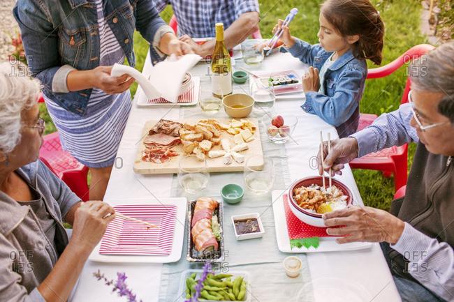 High angle view of family eating food on picnic table at backyard
